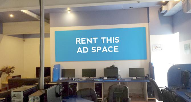 [Image: Ad space on a wall in an internet cafe]